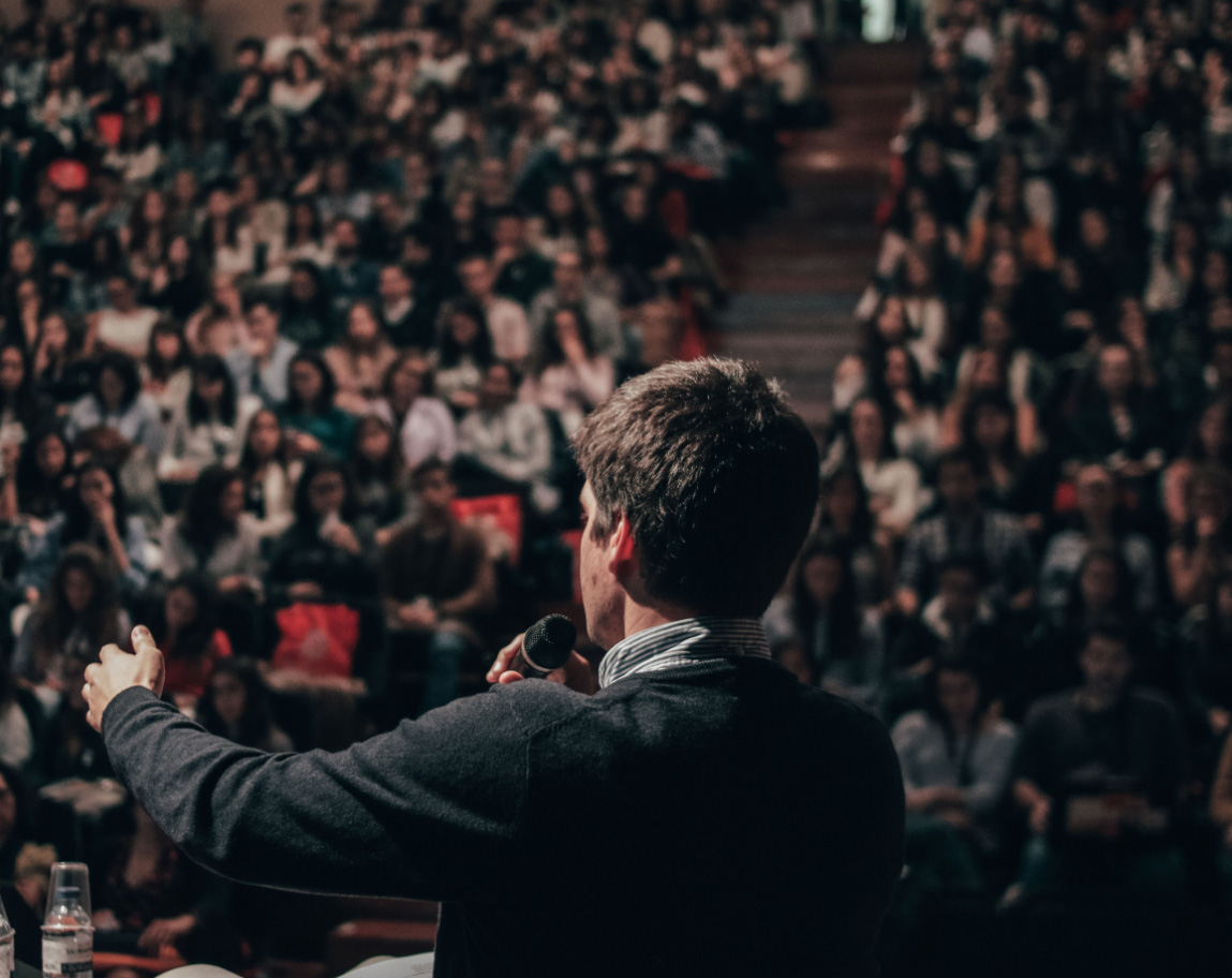 A man giving a speech to a crowded auditorium